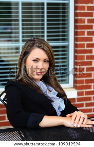 Attractive Professional Business Woman Sitting Outside Relaxing With a Window Behind Her - stock photo