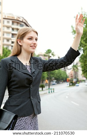 Attractive professional business woman standing in the middle of a financial city street calling a taxi and holding up her arm. Business people commuting and using public transport to get to work. - stock photo