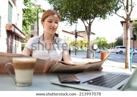 Attractive professional young business woman sitting at a coffee shop reading a financial newspaper and drinking a hot beverage, with a laptop computer and smartphone technology, outdoors.  - stock photo