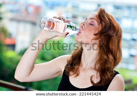 attractive red hair freckles woman drinks water from plastic bottle - stock photo