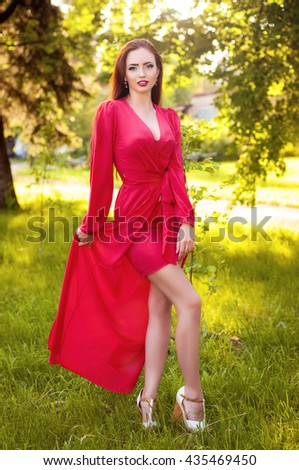 Attractive red hair girl enjoying nature. Beautiful young woman wearing long red dress - stock photo