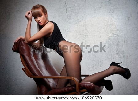 Attractive red hair model with black corset sitting provocatively on chair - gray background. Fashion portrait of a sensual woman - studio shot. Beautiful redhead female in black posing provocatively. - stock photo