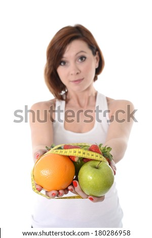 attractive red hair woman holding a mix of fruit  in hands bond with measure tape in slave to diet concept isolated on white background