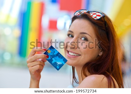 attractive red hair woman holding credit card - stock photo