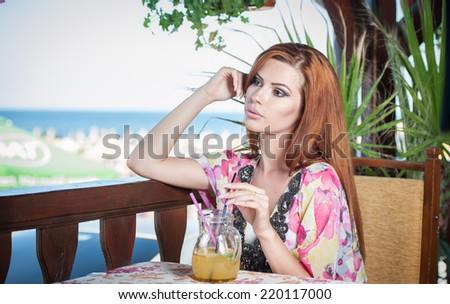 Attractive red hair young woman with bright colored blouse drinking lemonade on a terrace having blue sea in background. Gorgeous redhead model drinking fresh drink with straw in a summer day