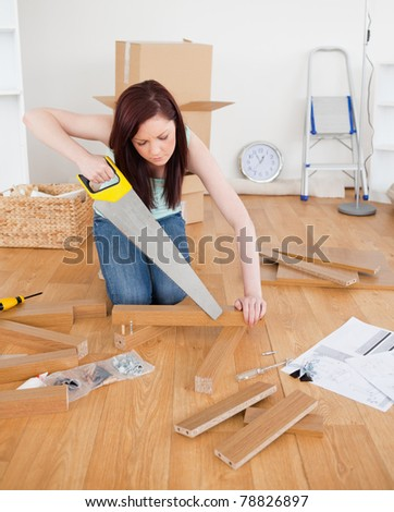 Attractive red-haired female using a saw for diy at home - stock photo
