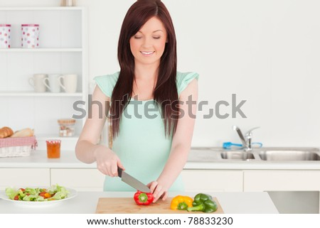 Attractive red-haired woman cutting some vegetables in the kitchen in her apartment