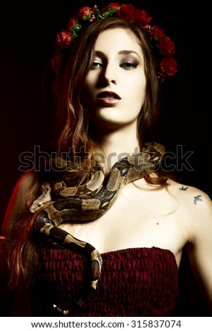Attractive red haired woman posing with boa constrictor - stock photo