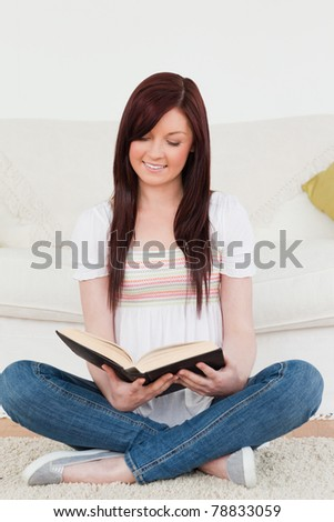 Attractive red-haired woman reading a book while sitting on a sofa in the living room
