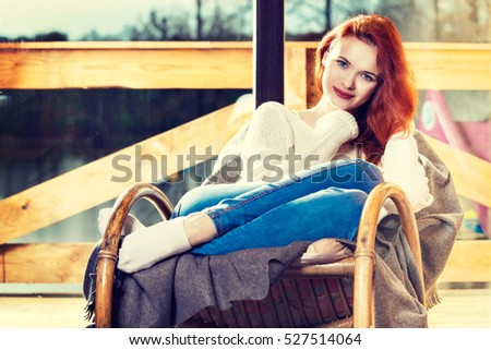 Attractive red-haired woman resting sitting on Rocking chair in front of window. Calm and coziness. Toned image