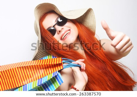 attractive redhair shopping woman wearing sunglasses and hat - stock photo