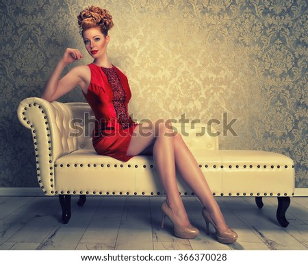 attractive redhaired woman in a red mini dress - stock photo