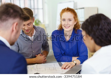 Attractive redhead businesswoman in a meeting with a team of young colleagues looking at the camera with a smile - stock photo