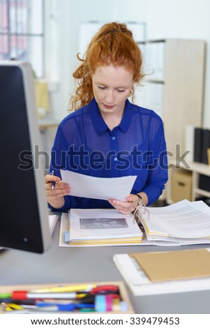 Attractive redhead businesswoman sitting at her desk in the office reading a document with a binder open in front of her
