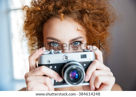 Attractive redhead curly young woman photographer using old camera - stock photo