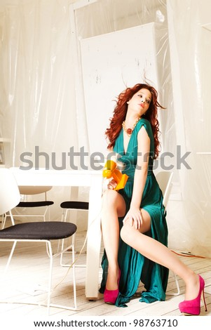 attractive redhead elegant woman sit in modern white apartment hold retro looking fan - stock photo