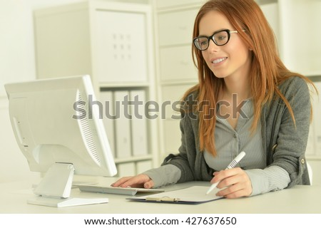 Attractive redhead woman in eyeglasses - stock photo