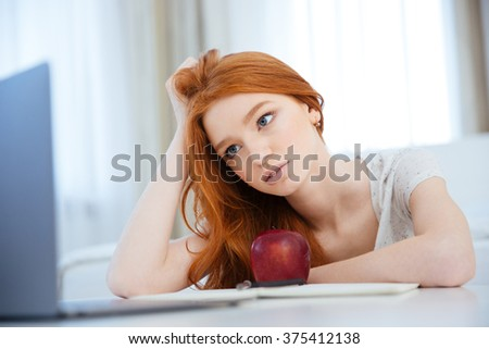 Attractive redhead woman looking on laptop computer screen at home - stock photo