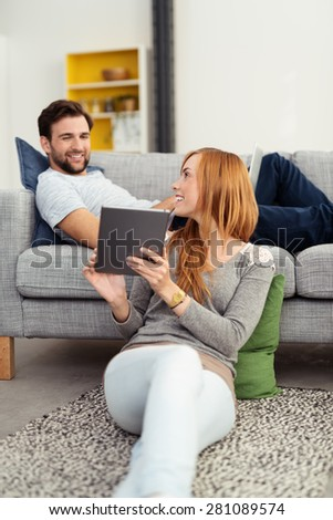 Attractive redhead woman relaxing on the floor at home showing her tablet computer to her husband as he reclines on the sofa above her - stock photo