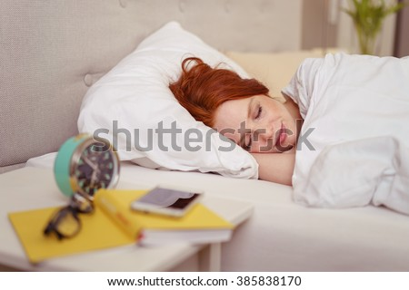 Attractive redhead woman sleeping in bed with a serene smile on her face and an alarm clock on the table alongside
