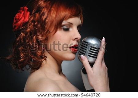 Attractive redhead woman with retro microphone - stock photo