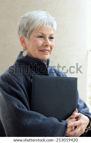 Attractive Retired Senior Citizen Business Woman Who is Mature and Pretty and Smiling and Holding a Folder