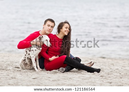 attractive romantic couple with a dog having fun on the beach