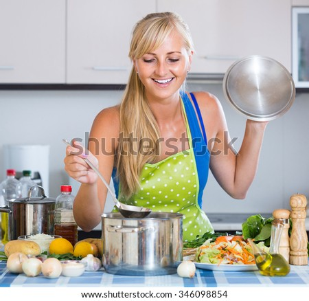 Attractive russian girl with long hair cooking vegetables in kitchen
