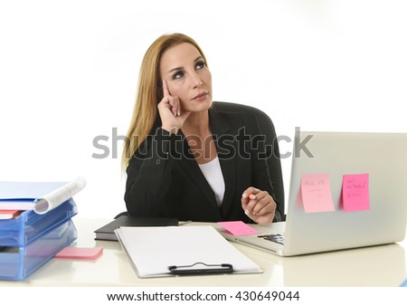attractive 40s blond businesswoman working at office laptop computer sitting on the desk absent minded and thoughtful as if thinking of important business isolated on white background - stock photo