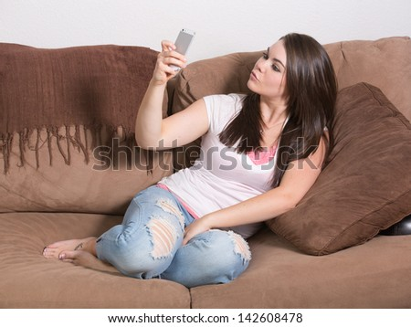 Attractive 20's woman taking self portrait with smart-phone while making a silly duck face. - stock photo