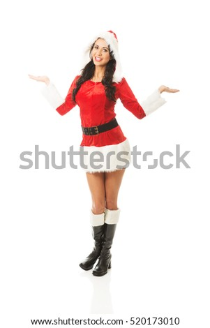 Attractive santa woman standing, holding something invisible in both hands