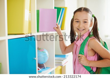 Attractive schoolchild looking at camera in classroom - stock photo