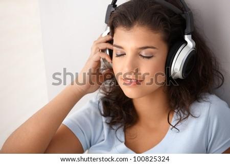 Attractive schoolgirl listening music through headphones, eyes closed. - stock photo