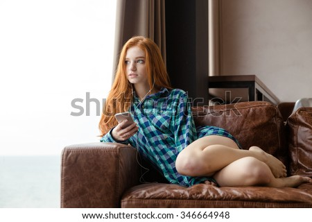 Attractive seductive young lady with long red hair in plaid shirt sitting on sofa and listening to music - stock photo