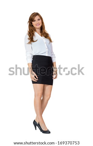 Attractive self-assured trendy young businesswoman wearing high heels and a black miniskirt standing with folded arms smiling at the camera, side view isolated on white