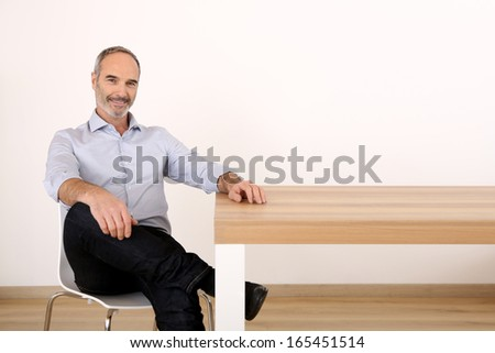 Attractive senior businessman sitting at table - stock photo