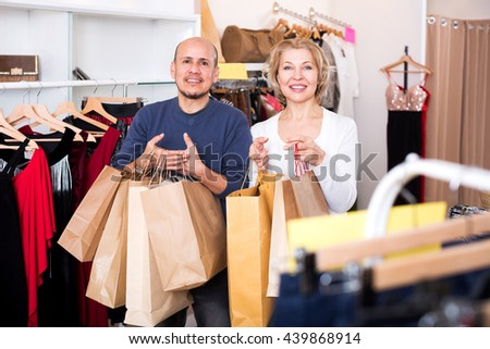 Attractive senior spouses carrying bags with purchases in clothing store