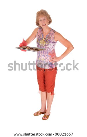 attractive senior with tray of cookies on a white background