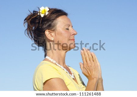 Attractive senior woman peaceful and happy relaxed  meditating outdoor, isolated with blue sky as background and copy space. - stock photo