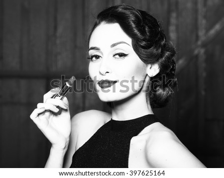 Attractive sensual fashionable retro elegant young adult woman with classic hairstyle and red lips holding lipstick in evening dress indoor on wooden background, horizontal picture