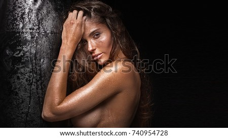 Attractive sensual woman with drops of water on body, looking at camera.