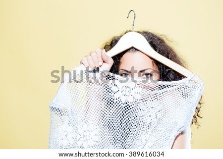 Attractive sensual young brunette woman with long curly hair standing topless with knitted white blouse in hands on hanger indoor on studio on yellow background, horizontal picture - stock photo