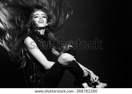 Attractive sensual young fashionable woman in stylish cloth and torn jeans with long beautiful hair sitting indoor on studio background black and white, horizontal picture - stock photo