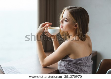Attractive sensual young woman in grey coverlet sitting at the table and drinking coffee