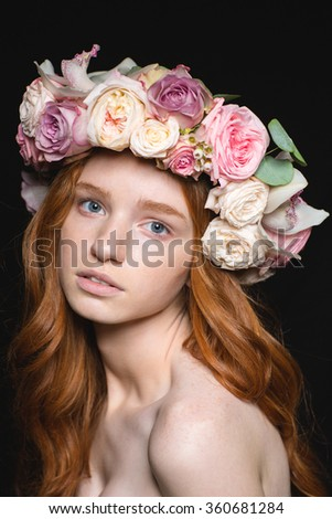 Attractive sensual young woman with long wavy hair in rose wreath over black background - stock photo