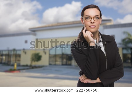 Attractive Serious Mixed Race Woman In Front of Vacant Commercial Retail Building. - stock photo
