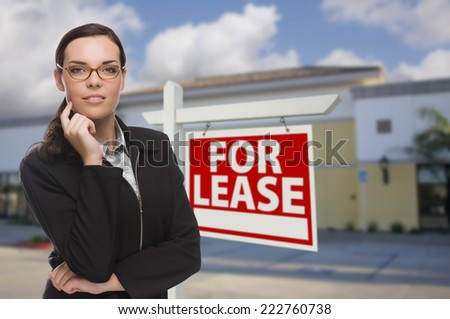 Attractive Serious Mixed Race Woman In Front of Vacant Retail Building and For Lease Real Estate Sign. - stock photo