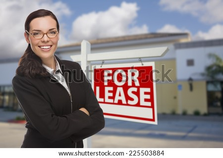 Attractive Serious Mixed Race Woman In Front of Vacant Retail Building and For Lease Real Estate Sign.