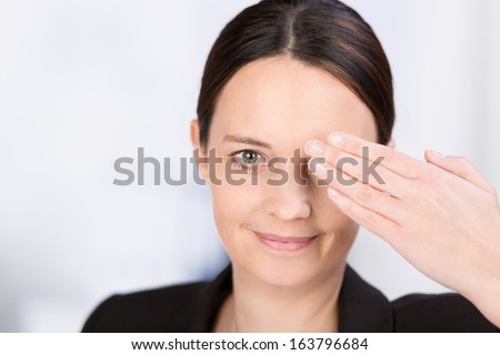 Attractive serious young woman covering one eye with her hand while looking at the camera with the other eye and smiling - stock photo