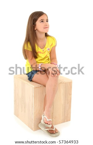 Attractive seven year old american girl sitting on wooden box over white background. - stock photo